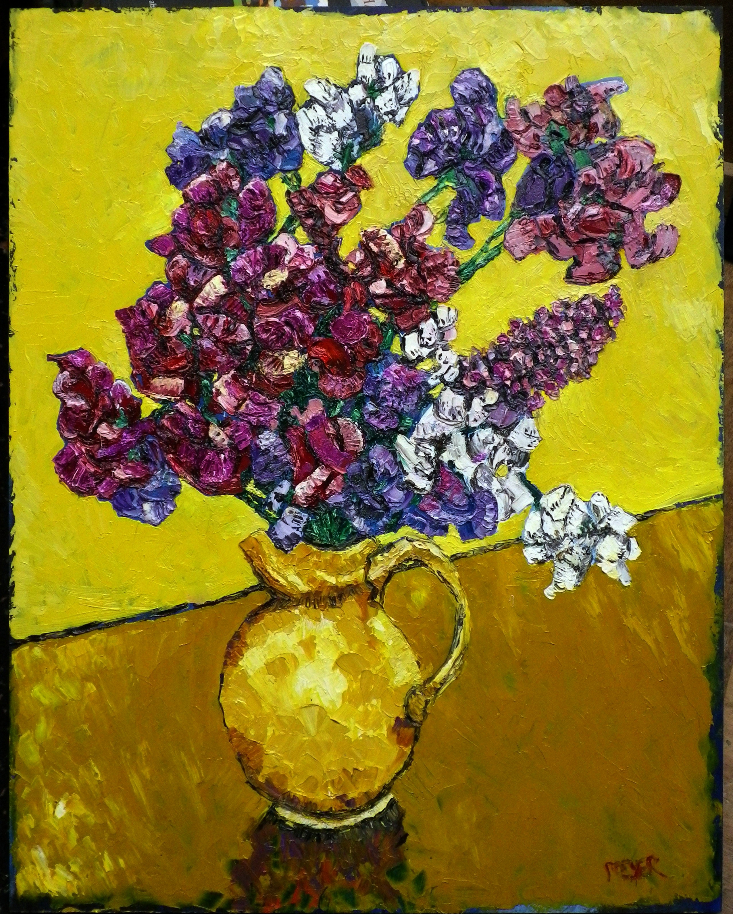 Sweetpeas with a buddleia spray in a yellow jug.