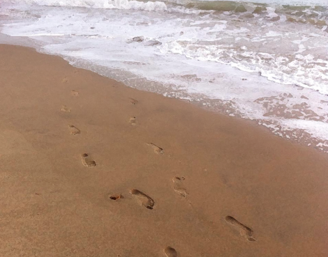 Footprints in sand by the sea